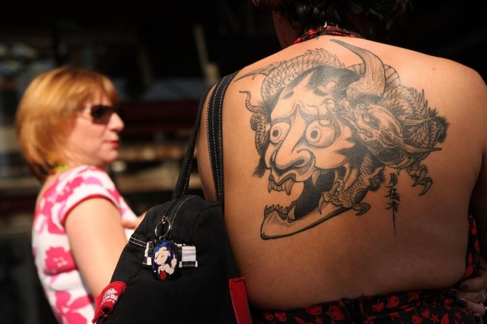 12) Женщина демонстрирует свою татуированную спину на пятом лондонском фестивале тату. Неотъемлемой частью фестиваля стали выборы королевы тату - Tattoo Queen. Принять участие в состязаниях может любая женщина, у которой на теле есть татуировка. (Photo by Oli Scarff/Getty Images)