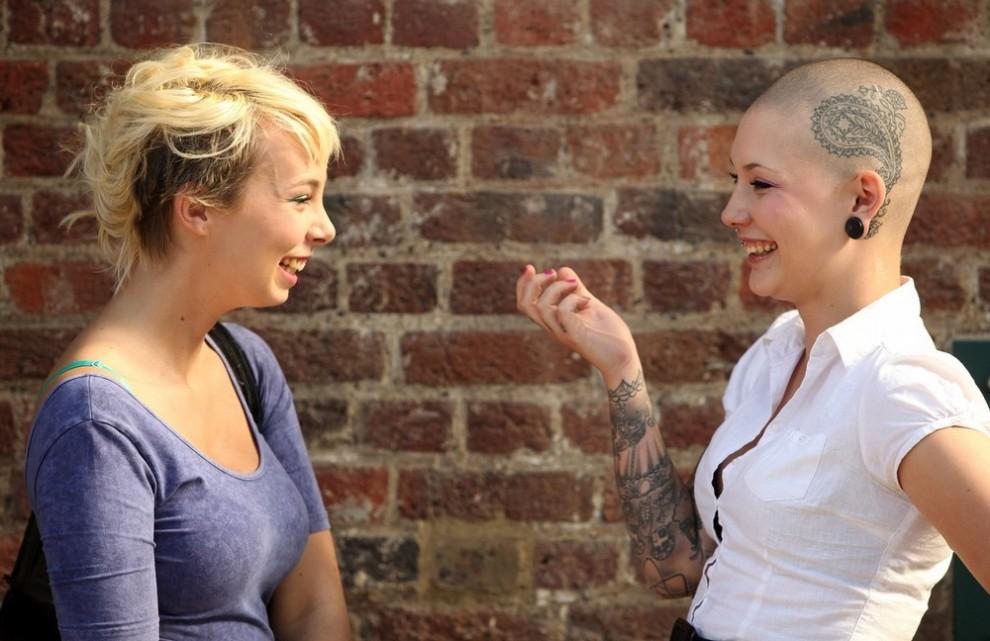 9) Любительницы тату Камилла Кайни (справа) и Чарли Кемп болтают в день открытия пятого лондонского фестиваля тату, состоявшегося в эти выходные в табачном доке в Ист-Энде. (Photo by Oli Scarff/Getty Images)