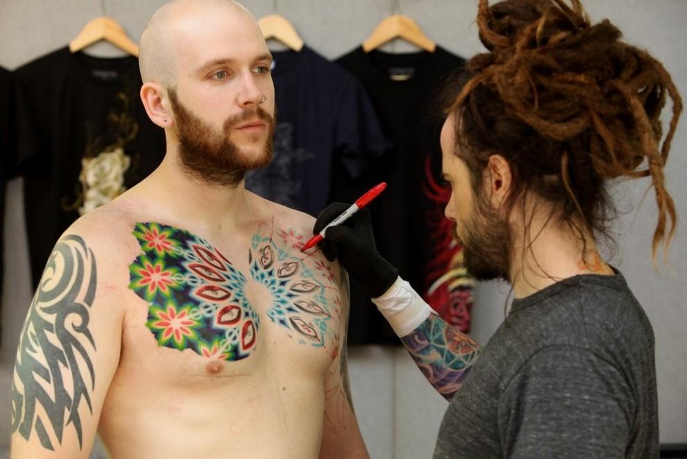 6) Татуировщик делает эскиз татуировки на груди мужчины в день открытия пятого Лондонского Фестиваля Тату, в Ист-Энде. (Photo by Oli Scarff/Getty Images)