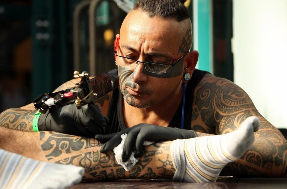 2) Лондон, Англия - 25 сентября: Татуировщик набивает рисунок на голень посетителя Лондонского Фестиваля Тату, который прошел в лондонском Ист-Энде с 25 по 27 сентября. Фестиваль прошел в «Tobacco Dock» - бывшем здании склада, построенном в начале 19 века. (Photo by Oli Scarff/Getty Images)