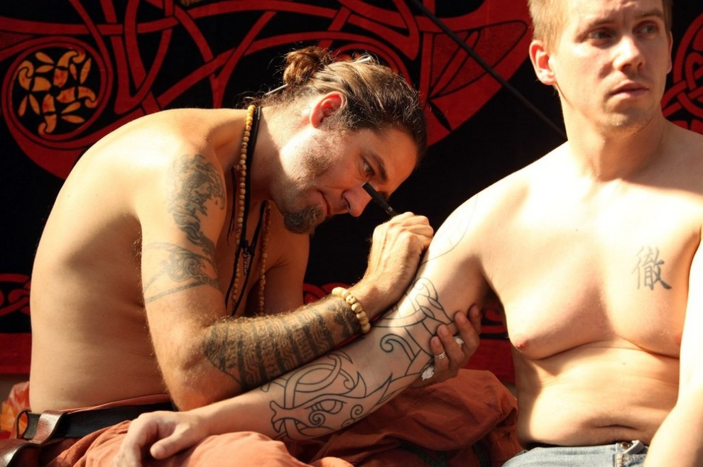 1) Лондон, Англия - 25 сентября: Татуировщик делает эскиз татуировки на руке клиента в день открытия пятого Лондонского Фестиваля Тату, в Ист-Энде. Ежегодный фестиваль является одним из главных в Европе событий, связанных с тату и другими модификациями тела. В  прошлом году в фестивале приняли участие 20 тысяч посетителей. (Photo by Oli Scarff/Getty Images)