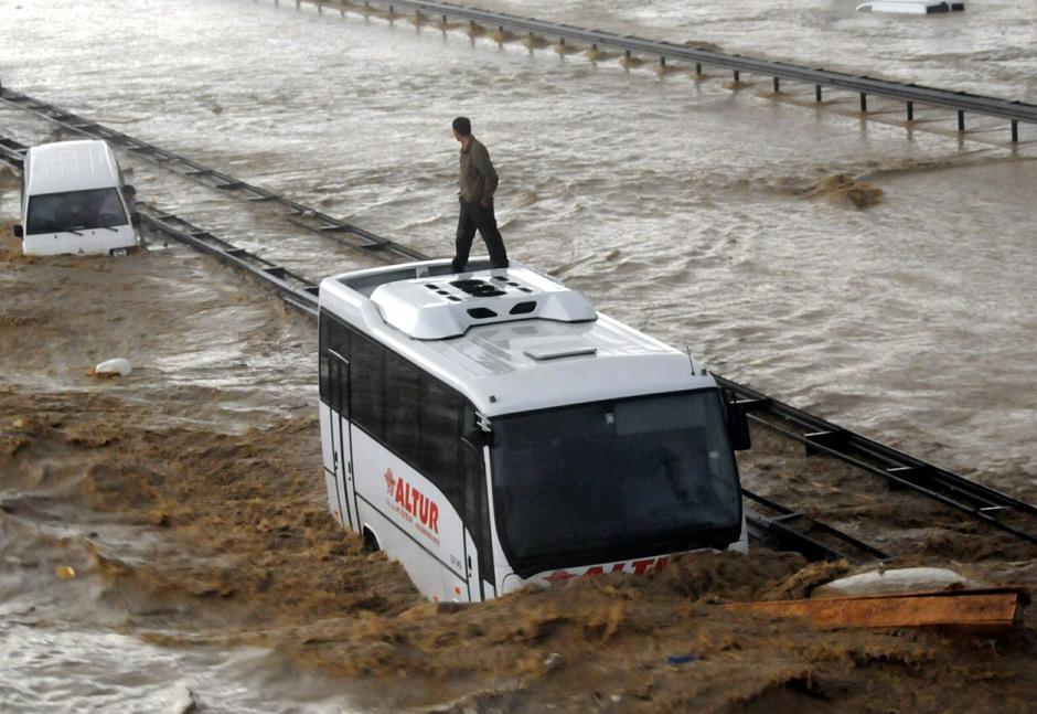 5) Человек на частично затопленном автобусе на стамбульском шоссе ждет спасателей.