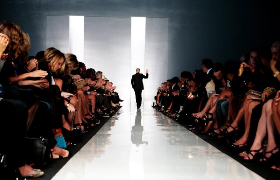 4) Майкл Корс приветствует публику после показа своей коллекции.