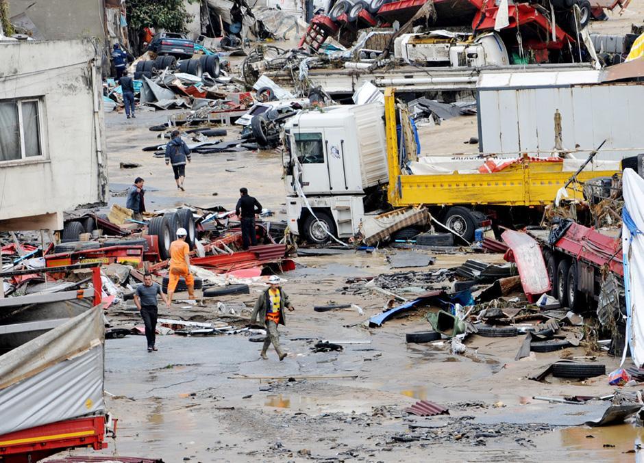 8) Спасатели и местные жители собираются около поврежденных автомобилей в ходе спасательных операций в Стамбуле.