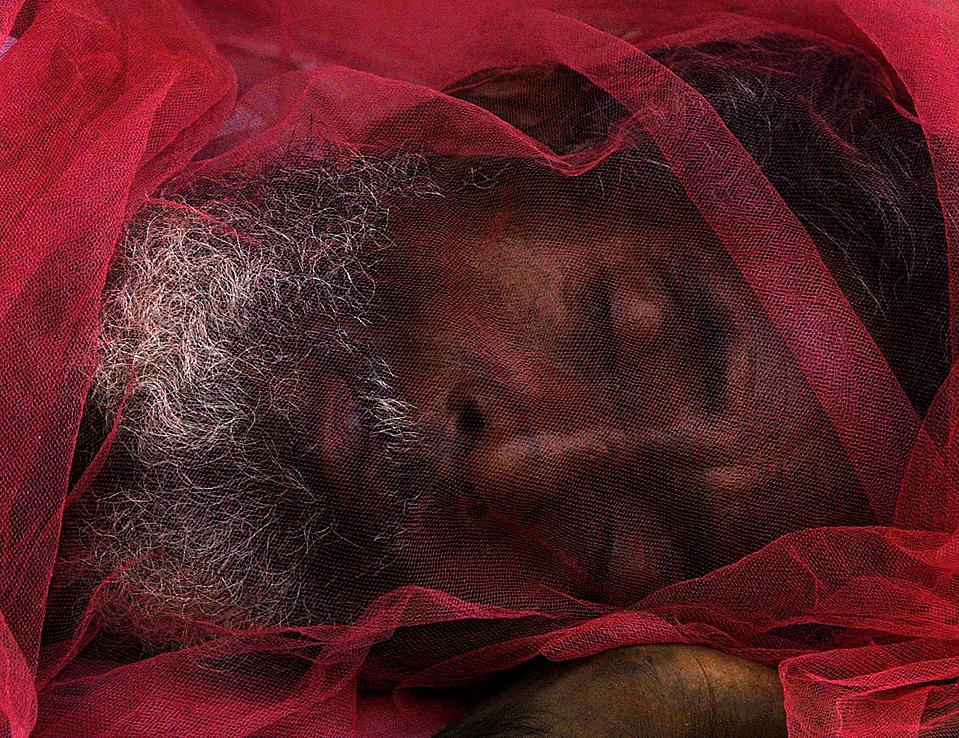 2) Человек с москитной сеткой на лице спит на улице в пакистанском городе Карачи. (Akhtar Soomro/Reuters)