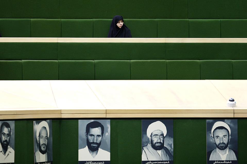 8) Иранская женщина следит за дебатами во время открытой сессии парламента в Тегеране, темой которой стал предлагаемый президентом Махмудом Ахмадинежадом кабинет министров из 21 члена. (Ниже представлены фотографии ныне действующих парламентариев). Некоторые парламентарии считают, что кандидаты не имеют необходимой квалификации и были выбраны исключительно из-за своей лояльности Ахмадинежаду. (Vahid Salemi/Associated Press)