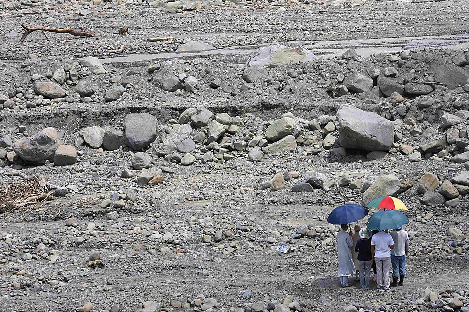 12) Люди стоят во время минуты молчания в память о жертвах оползня в тайваньской деревне Hsiaolin, в то время как Далай-лама, (не видно на фото), молится за жертв тайфуна «Моракот» понедельник. Духовный лидер Тибета в изгнании посетил Тайвань, опустошенный наводнением, с гуманитарным визитом. Китай осудил этот визит. (Nicky Loh/Reuters)