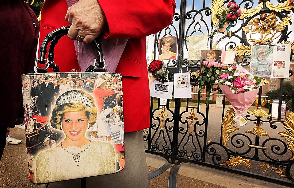 13) Женщина держит сумочку с портретом Диана, принцессы Уэльской, перед воротами в Кенсингтонский дворец в Лондоне. Поклонники принцессы собрались, чтобы помянуть Диану, которая погибла в автокатастрофе в Париже 12 лет назад. (Peter MacDiarmid/Getty Images)