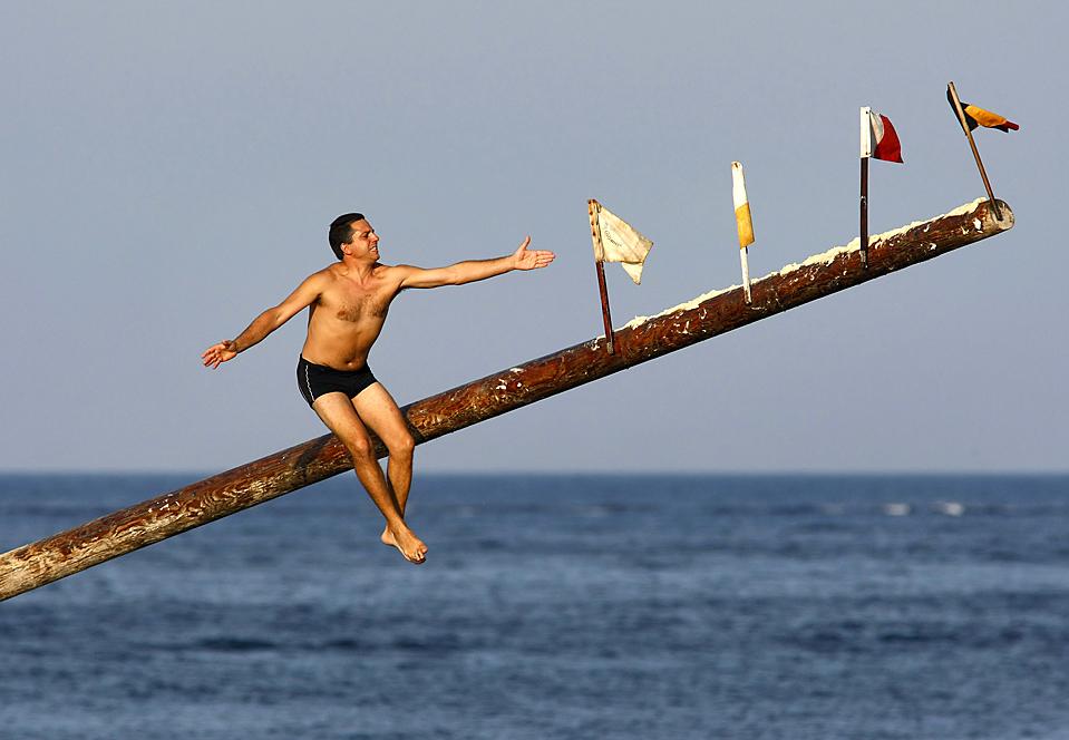 16) Участник соревнований скользит вниз по шесту, обмазанном жиром во время религиозного праздника Св. Джулиана в городе Сент-Джулианс на Мальте. Во время соревнования, участники стараются установить флагами, чтобы выиграть призы. (Darrin Zammit Lupi/Reuters)