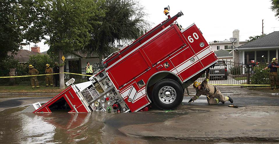 5) Пожарный из Лос-Анджелеса заглядывает под пожарную машину, которая застряла в водосточном колодце в районе Лос-Анджелеса Веллей Вилладж. Четверо пожарных чудом избежали травм после того, как 22-тонная пожарная машина ушла в большую яму, причиной образования которой стала авария водопровода. (Nick Ut/Associated Press)