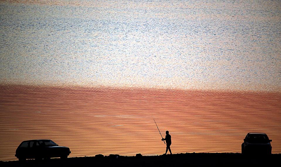 6) Рыбак идет вдоль озера на закате возле деревни Chenge в Болгарии. (Petar Petrov/Associated Press)