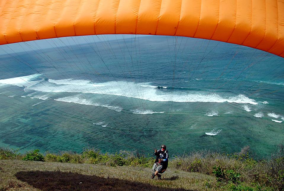 7) Мужчина прыгает с парапланом со склона в Timbis, Jimbaran, на индонезийском острове Бали. Парапланёры используют для подъема вверх воздушные потоки. (Sonny Tumbelaka/Agence France-Presse/Getty Images)