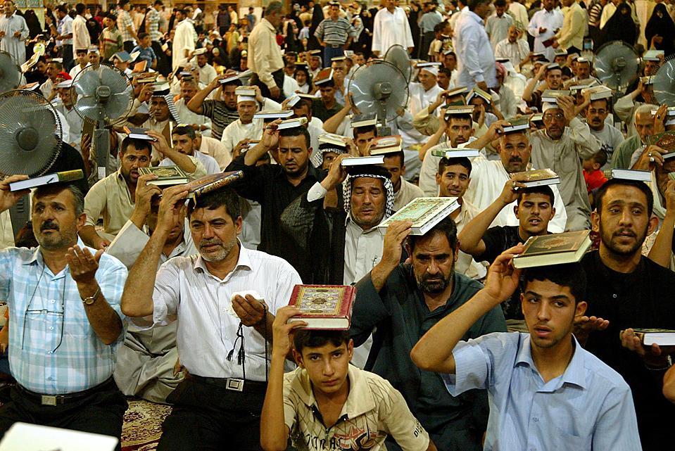 8) Шиитские мусульмане держат Кораны у головы во время молитвы в ночь предопределения (Лайлат-уль-Кадр). Считается, что именно в эту ночь Аллах впервые показал Коран пророку Мухаммеду. (Qassem Zein/Agence France-Presse/Getty Images)