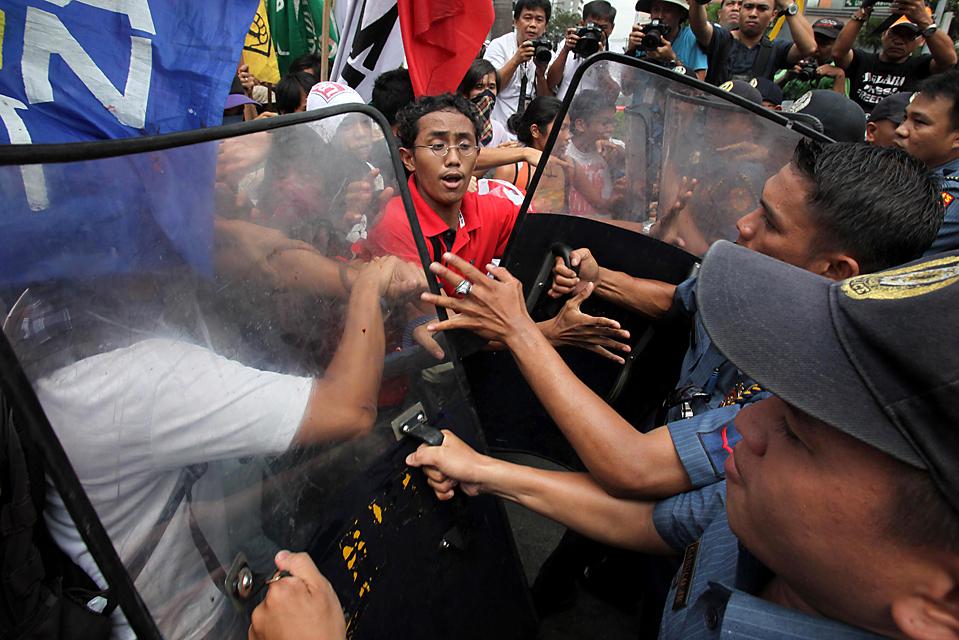7) Протестующие во время стычки с полицией, при их попытке силой проникнуть на территорию посольства США в Маниле. Участники акции протеста выступали против продолжающегося присутствия американских войск на Филиппинах, которые находятся там с целью борьбы с терроризмом. (Bullit Marquez/Associated Press)