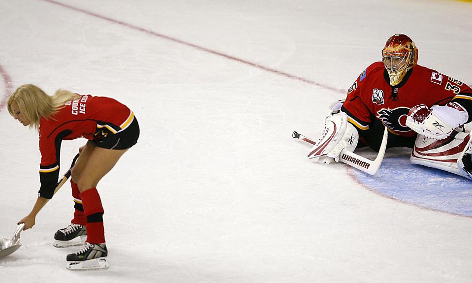 16) Вратарь команды «Calgary Flames» Леланд Ирвинг наблюдает за тем как девушка из персонала команды убирает снег со льда в перерыве после второго периода предсезонки НХЛ против «Edmonton Oilers» в Калгари, Альберта, Канада. (Todd Korol/Reuters)