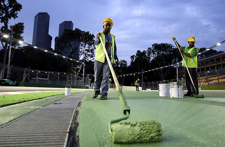 12) Рабочий красит трек в Сингапуре во время подготовки ко вторым ночным гонкам Формулы Один, запланированным на 27 сентября. (Wong Maye/Associated Press)