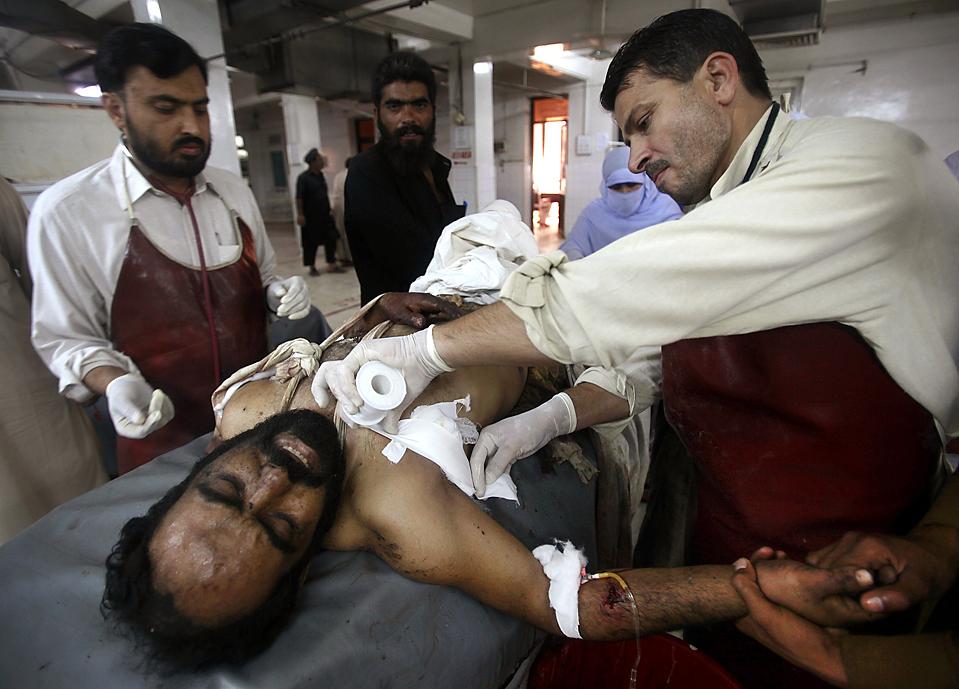 6) Персонал больницы в Пешаваре помогает одному из раненых во время атак террористов-смертников. В результате погибли, по меньшей мере, 29 человек и были уничтожены две гостиницы в пакистанском городе Кохат. (Fayaz Aziz/Reuters)