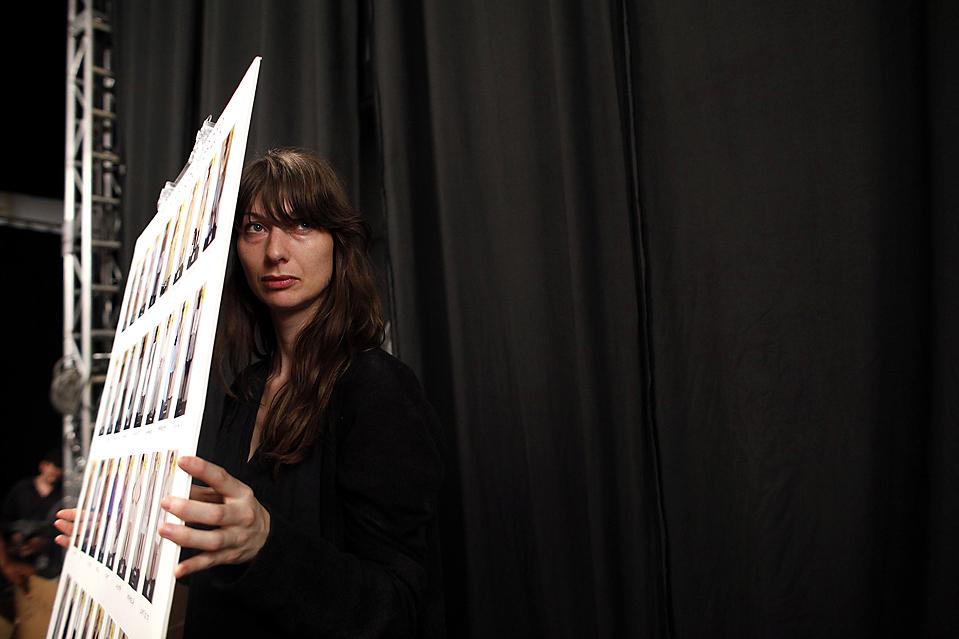 4) Женщина держит доску с фотографиями моделей в нарядах коллекции Isaac Mizrahi весна 2010 перед показом на Неделе моды в Нью-Йорке. (Eric Thayer/Reuters)