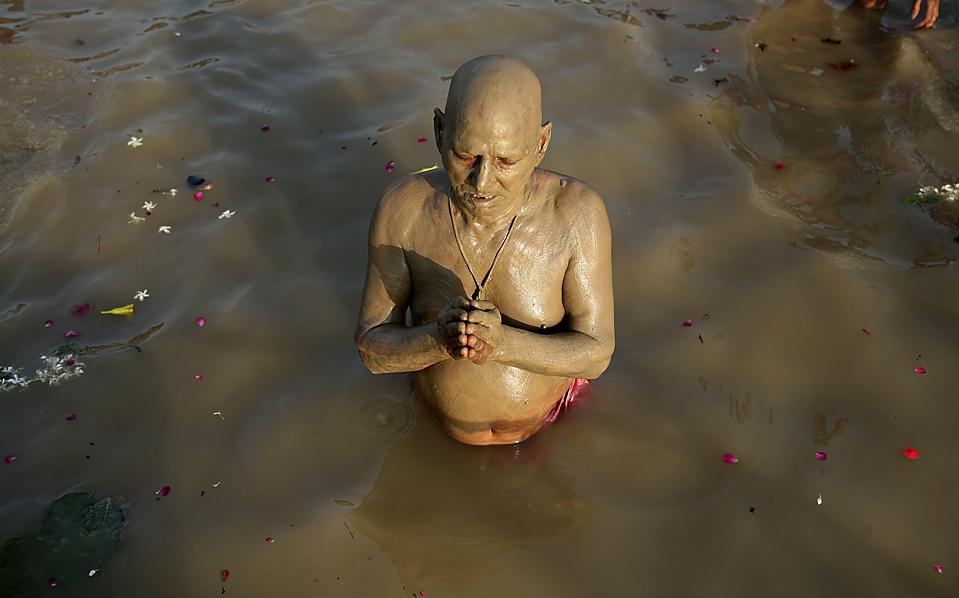 1) Индус выполняет Тарпан, ритуал, цель которого – упокой душ предков. Снимок сделан в Аллахабаде, Индия. (Rajesh Kumar Singh/Associated Press)
