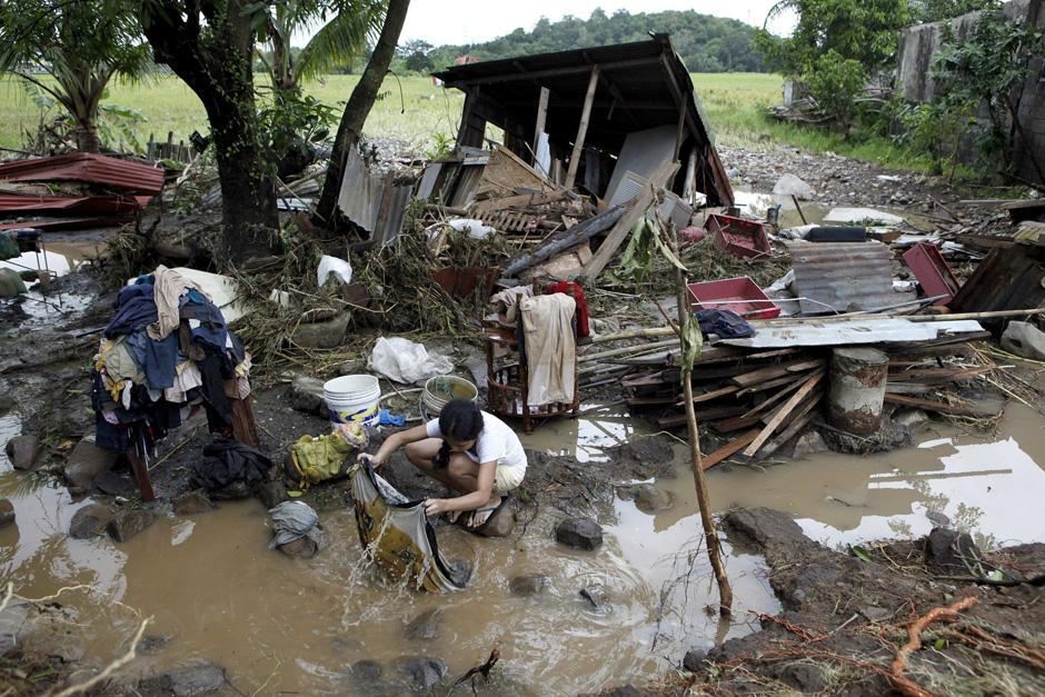 31) Женщина стирает одежду, которую вынесла из своего затопленного дома в городе Пилила Ризал, к востоку от Манилы.