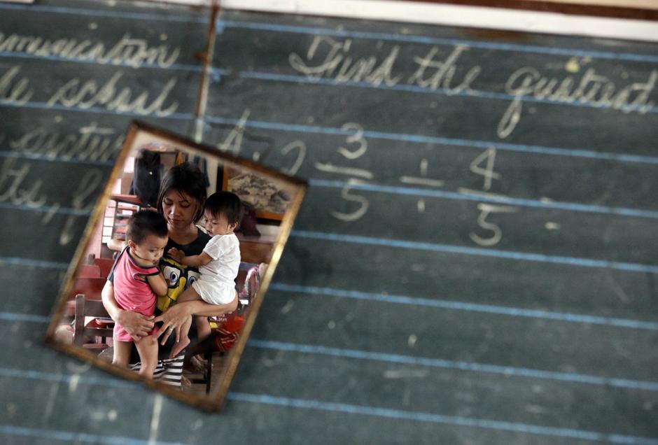 33) Мать несет детей в здании школы, которое используется как эвакуационный центр для лиц, пострадавших от наводнения. Снимок сделан в городе Танай-Ризал, к востоку от Манилы.