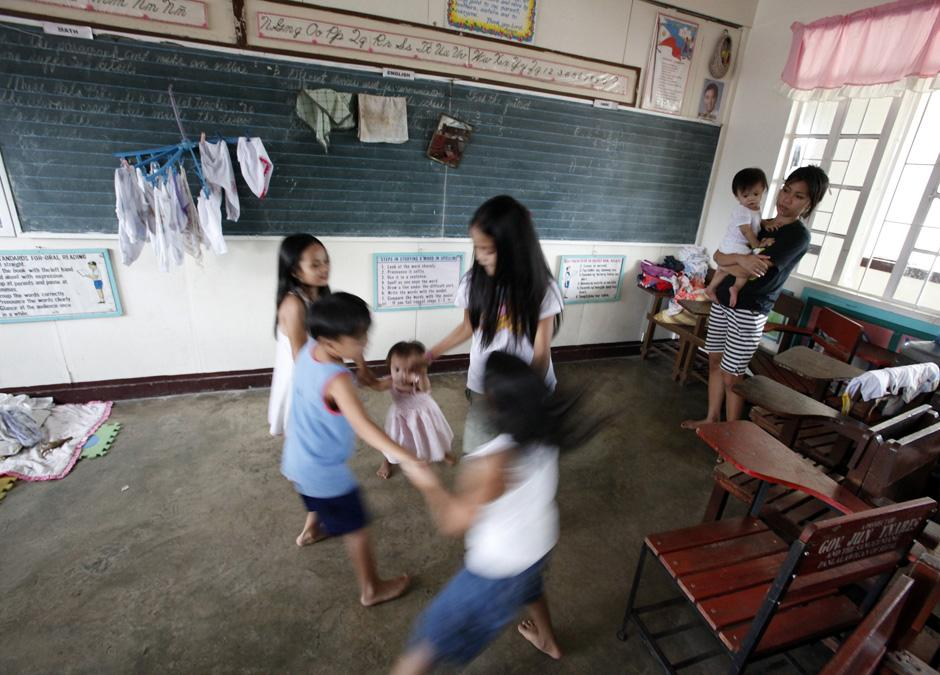30) Дети играют в здании школы, которое используется как эвакуационный центр для лиц, пострадавших от наводнения.