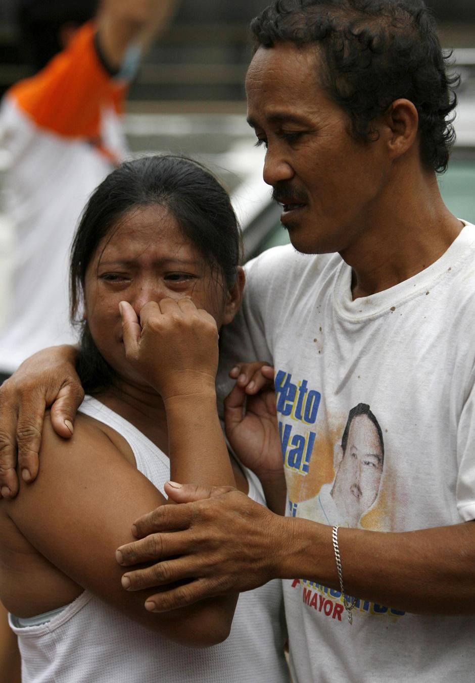 29) Родственники услышали весть о смерти своего близкого человека, погибшего в результате тайфуна Ketsana. Снимок сделан в морге города Танай, Ризал востоку от Манилы.