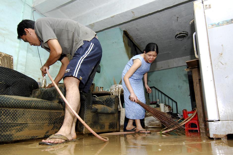 27) Местные жители убирают свои дома после наводнения вызванного тайфуном Ketsana.
