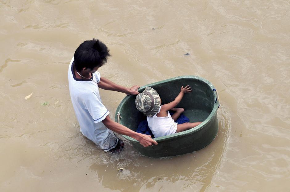 26) Местный житель толкает таз со своим маленьким братом после того, как наводнение причиной которого стал тайфун Ketsana, затопил город Пасай, к югу от Манилы.