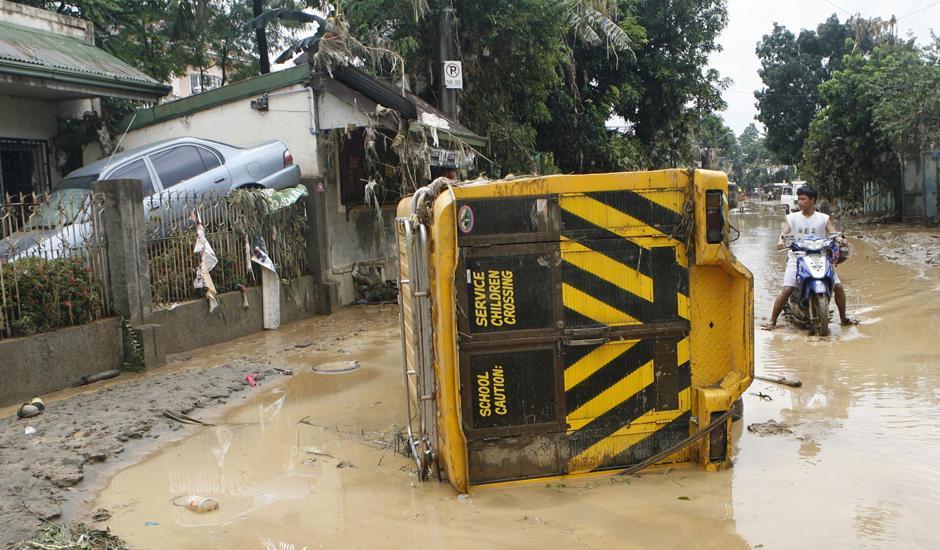 24) Человек смотрит на перевернутые после наводнения авто в жилом квартале города Маракина, расположенном к востоку от Манилы.