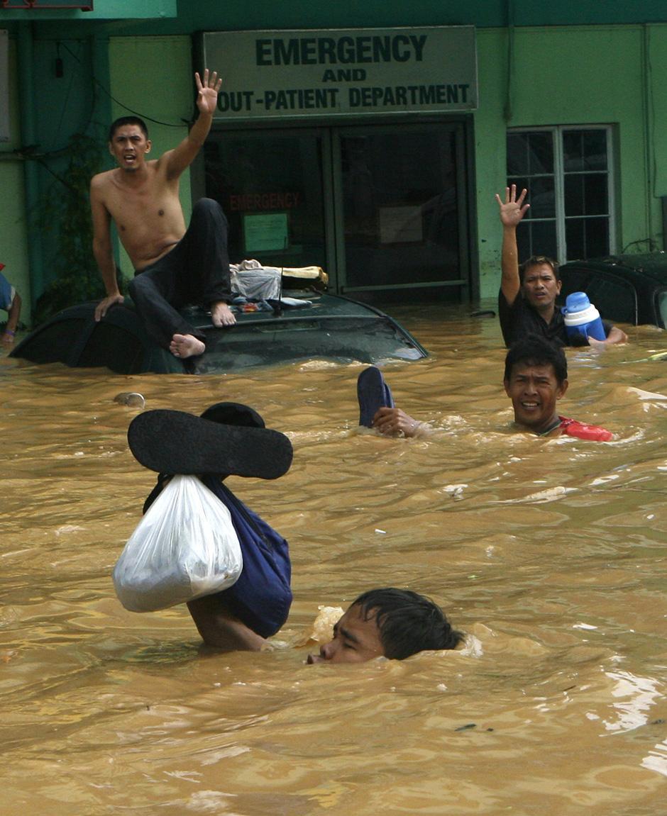 22) Жители ждут эвакуации после наводнения в Cainta Rizal, к востоку от Манилы.
