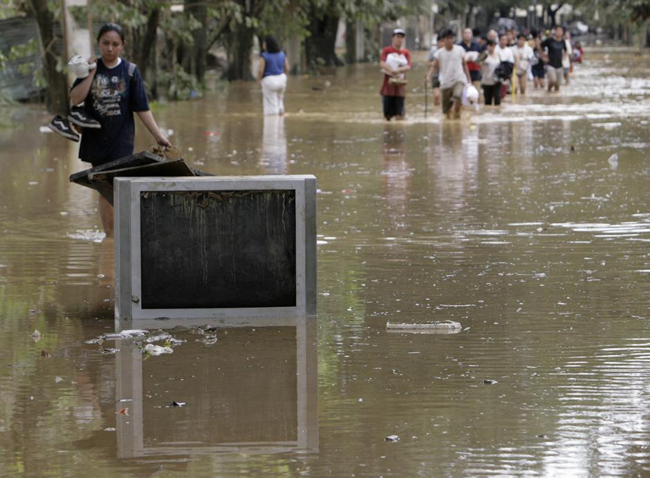 21) Телевизор на улице города Марикина в округе Манила. Местные жители покинули свои дома после ливневых паводков вызванных тайфуном.