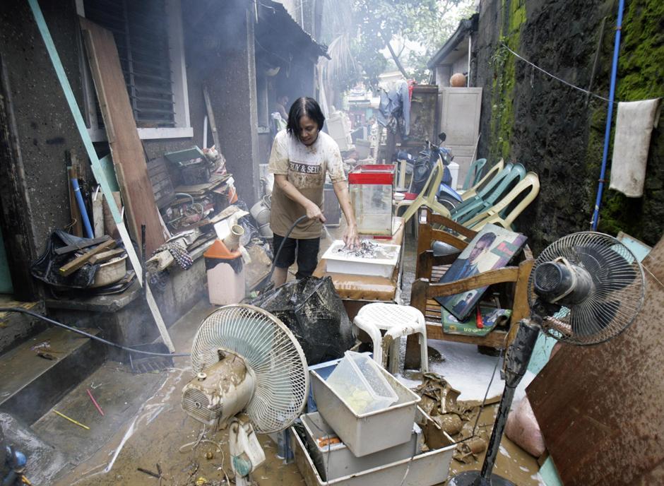 18) Местная жительница моет свои покрытые грязью пожитки. Снимок сделан после Ketsana в городе Марикина.