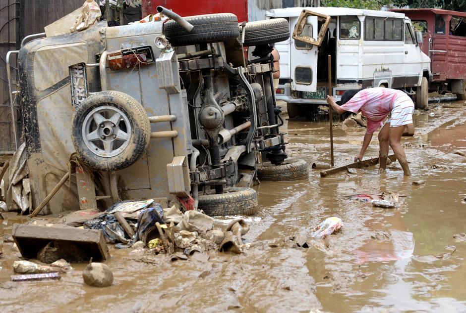 15) Жители убирают последствия  наводнения в пригороде Манилы, городе Марикина, в то время как вода постепенно отступает.