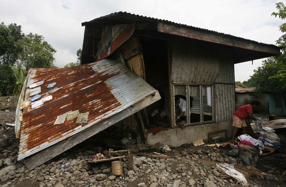 14) Люди осматривают руины своего дома в поисках ценных вещей. Снимок сделан после тайфуна Ketsana, в городе Араят, провинции Пампанга, к северу от Манилы.