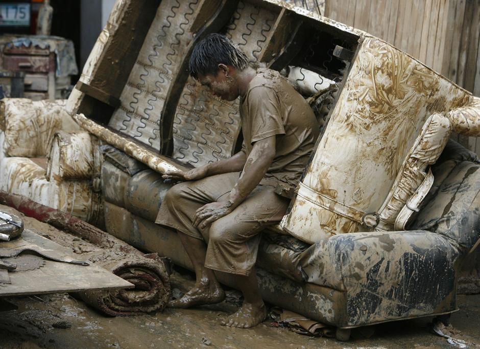 11) Человек присел отдохнуть во время уборки дома, который был затоплен наводнением. Снимок сделан после прохождения тайфуна  Ketsana, в городе Марикина к востоку от Манилы.