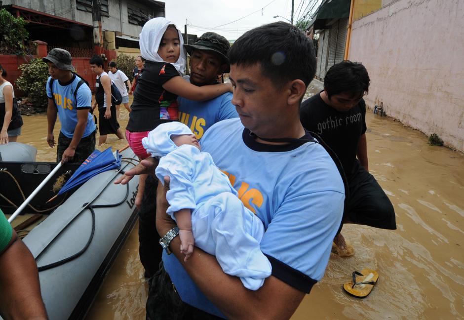 10) Спасатель несет ребенка в городе Pasig, недалеко от Манилы.