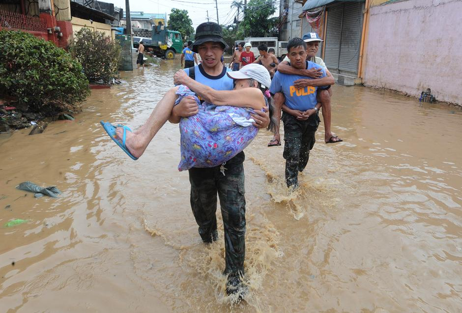 8) Спасатели несут пожилую пару по затопленной улице города Pasig, недалеко от Манилы.