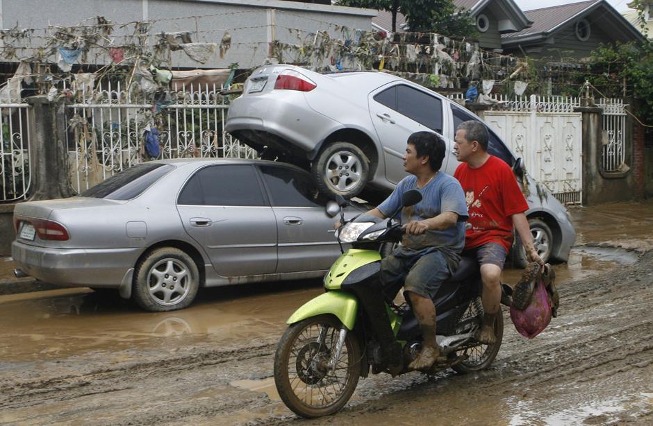 7) Мотоциклисты проезжают по улице жилого квартала в городе Маракине на фоне последствий наводнения вызванного тайфуном Ketsana, который на Филиппинах называют Ondoy.