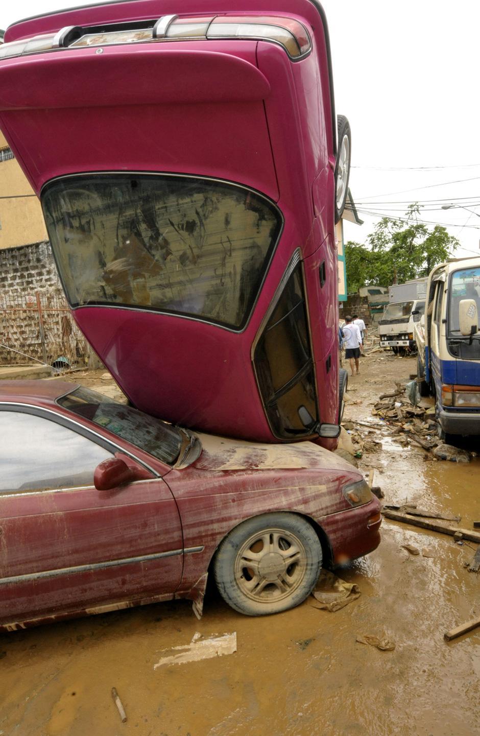 6) Перевернутые автомобили на затопленной дороге в городе Маракине, пригороде Манилы.