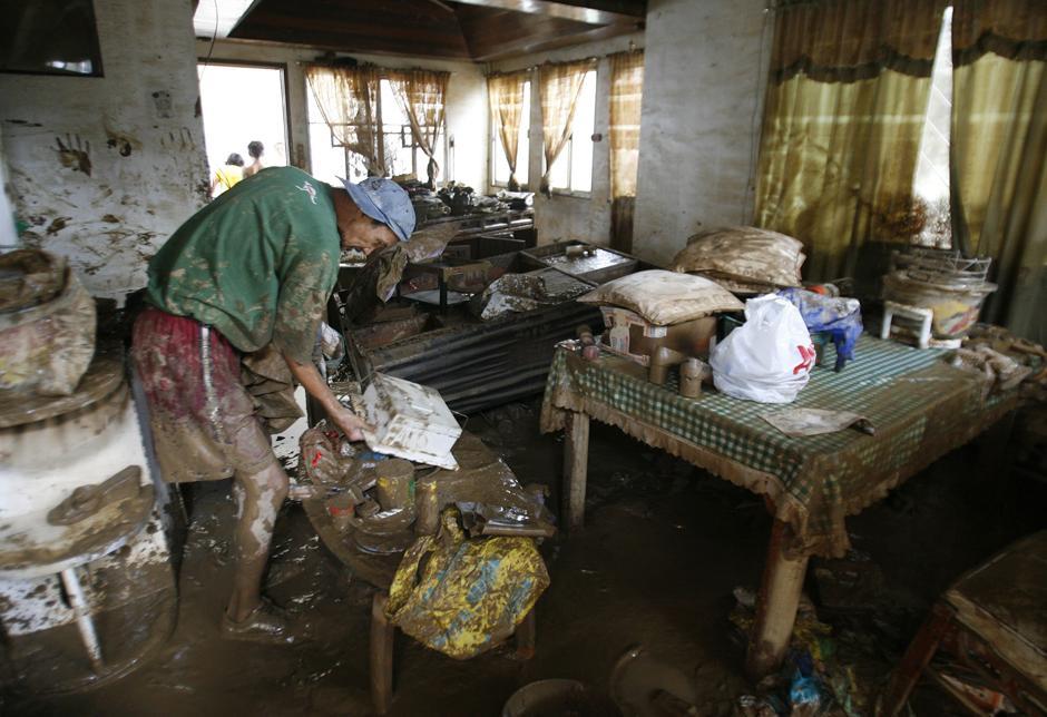 5) Мужчина собирает испачканные грязью вещи своей семьи в доме, затопленном после тайфуна Ketsana, в районе города Марикина где проживает средний класс.