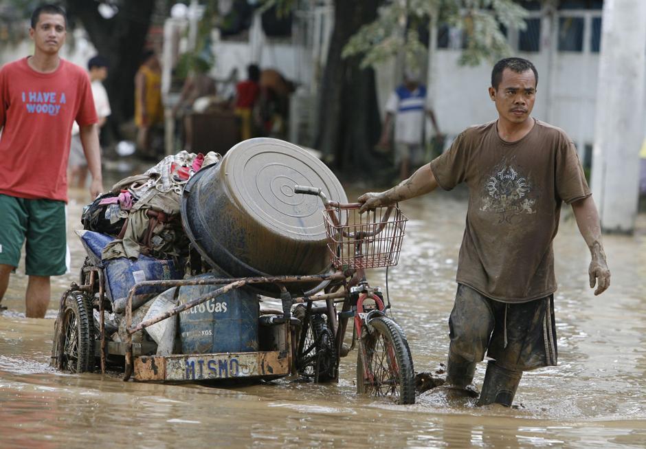 4) Человек тянет свою повозку велорикши груженую вещами. Снимок сделан в жилом районе затопленном из-за тайфуна Ketsana, в городе Марикина к востоку от Манилы.
