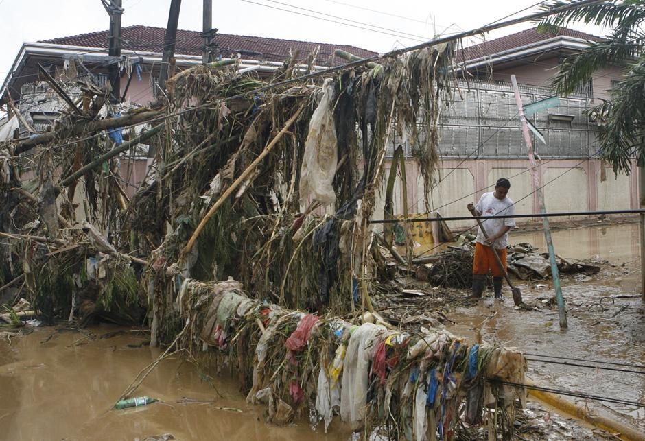 3) Уборка заваленной мусором дороги в Марикине после наводнения.