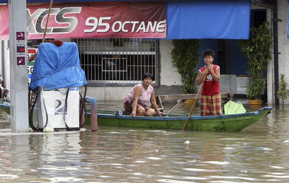 2) Жители плывут на каноэ мимо заправочной станции в Санта Роза Лагуна к югу от Манилы.