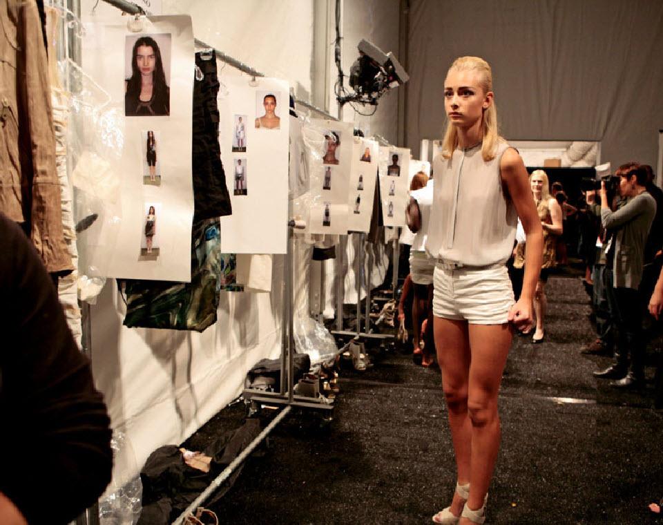 32) Девушка стоит около вешалки, где висят соответствующие модели одежды, по два комплекта одежды на каждую манекенщицу.