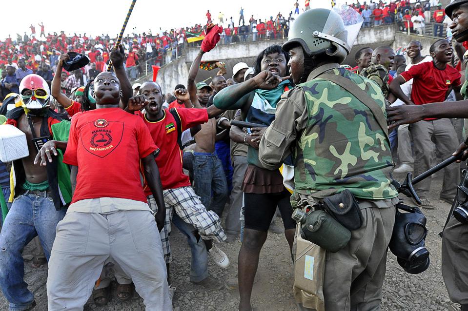 17) Полиция сдерживает фанатов мозамбикской сборной по футболу, чтобы не допустить беспорядков, после отборочного матча Чемпионата Мира 2010 между командами Мозамбика и Кении в Мапуту, Мозамбик, 6 сентября. (REUTERS/Grant Lee Neuenburg)