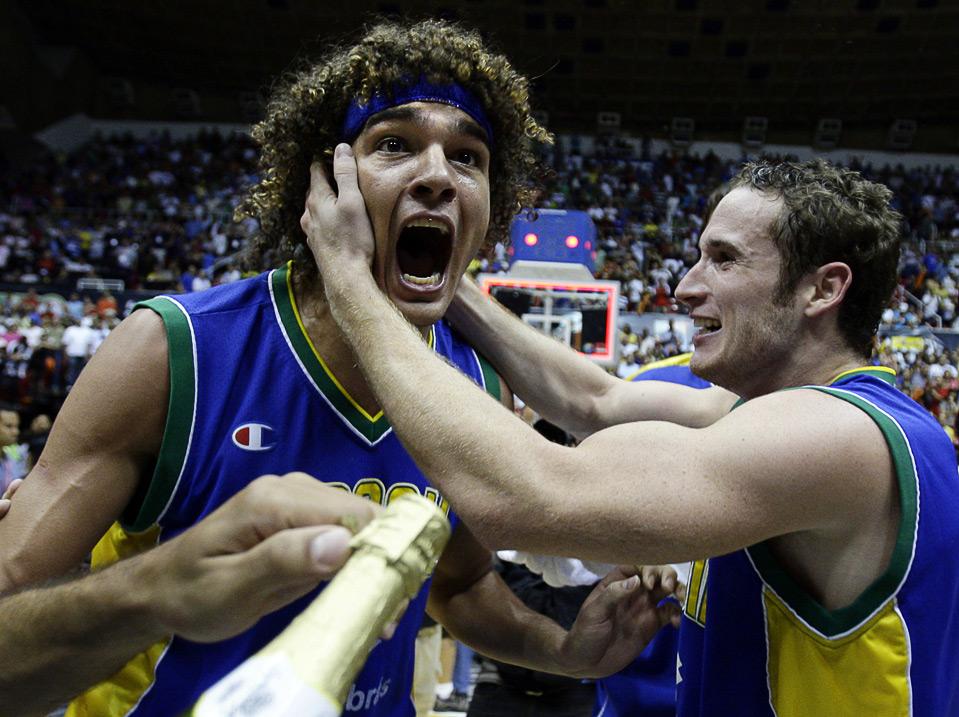 16) Бразилец Андерсон Вареао (слева) вместе с товарищем по команде радуется победе над командой Пуэрто-Рико в финальном матче Чемпионата Америки FIBA в Сан-Хуане, 6 сентября. (AP Photo/Andres Leighton)