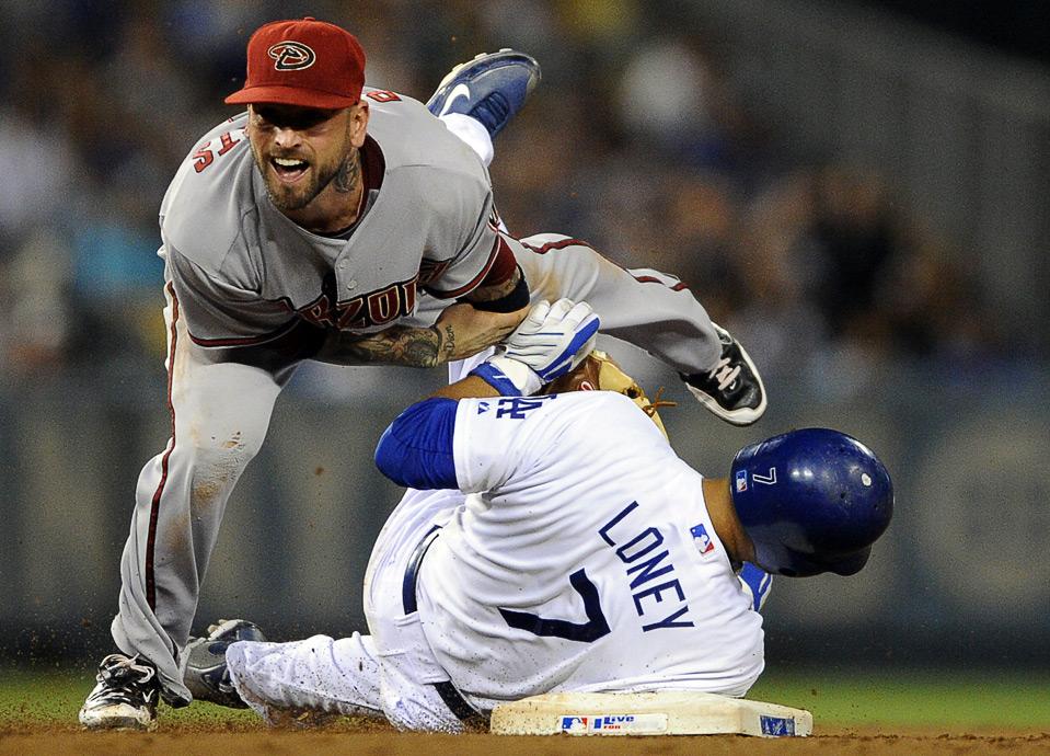14) Джеймс Луни из команды «Los Angeles Dodgers» останавливает двойной бросок Райана Робертса из «Arizona Diamondbacks» во время шестого иннинга бейсбольного матча MLB, Лос-Анджелос, 3 сентября. (AP Photo/Gus Ruelas)