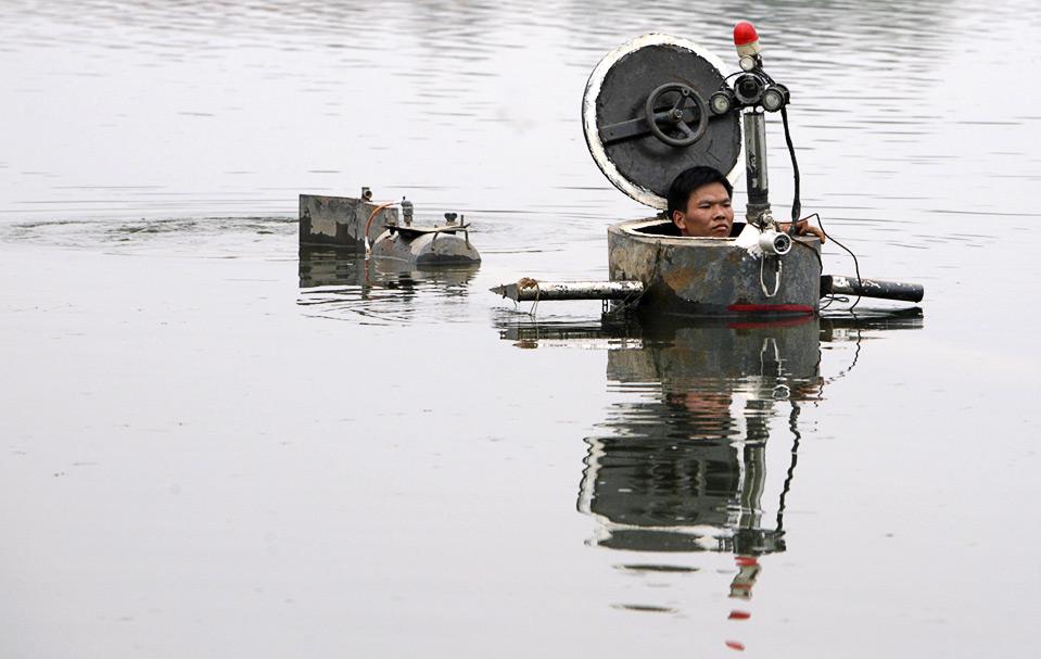 2) Изобретатель-любитель Тао Ксианги управляет самодельной подводной лодкой на озере неподалеку от Пекина, 3 сентября. Он собрал полнофункциональную подводную лодку, в которой есть перископ, управление глубиной погружения, электродвигатель, манометр и два гребных винта. Это все собрано из старой бочки для нефти и деталей, купленных на рынке подержанных товаров. Изобретателю потребовалось 2 года, чтобы собрать подводную лодку, обошлась она ему в 30,000 юаней ($4,385). (REUTERS/Christina Hu)