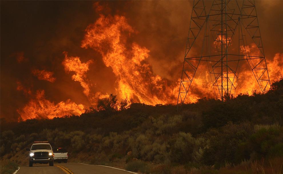5. Автомобиль едет мимо стены огня в Актоне, штат Калифорния, в северном районе Лос-Анджелеса 30 августа 2009 года. (REUTERS/Gene Blevins)